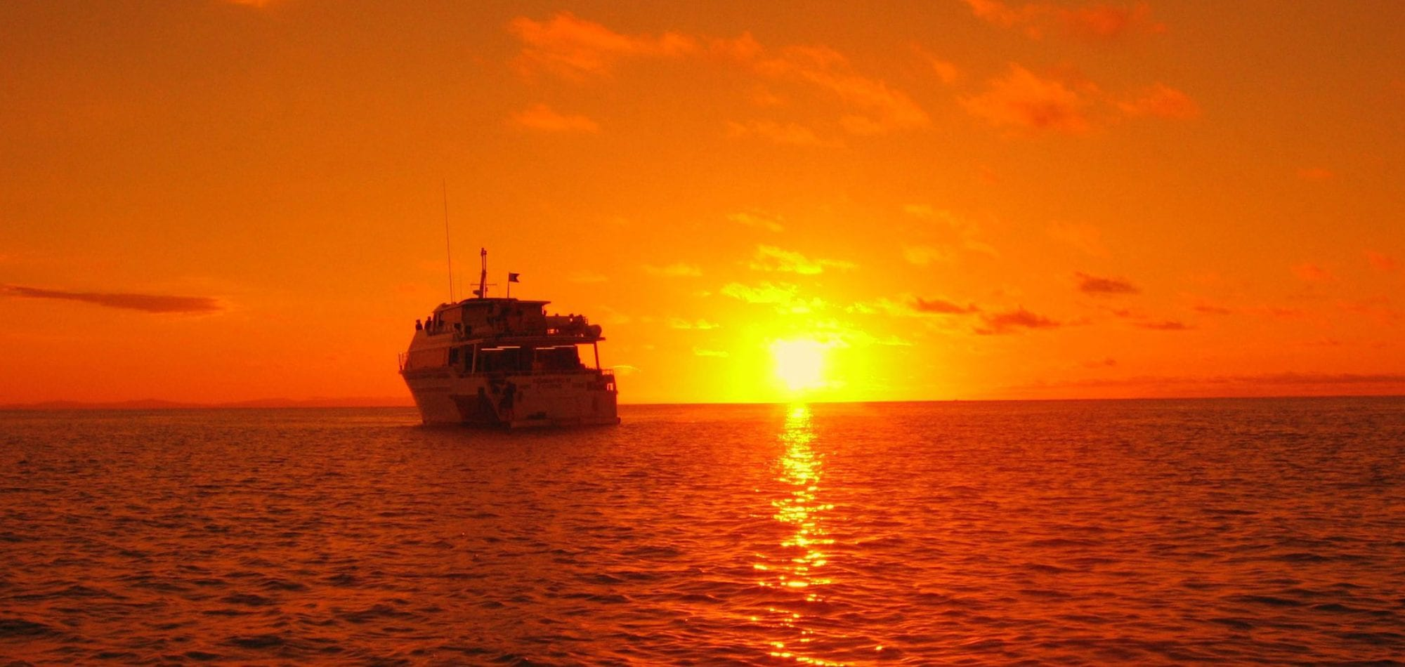 Cairns liveaboard scuba diving - sun setting behind Scubapro dive boat on the Great Barrier Reef
