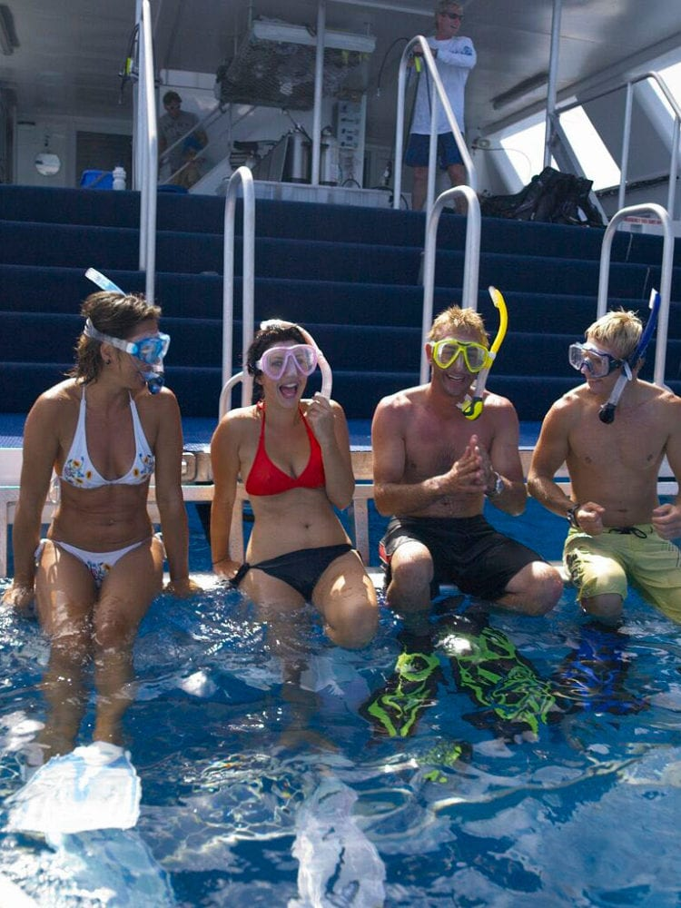 Cairns day trip - snorkelers enter the water from the back of the Tusa Dive boat